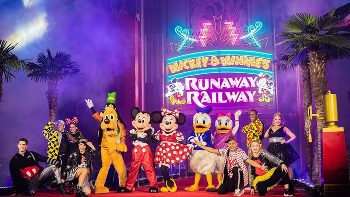 Mickey Mouse and several costumed characters and Disney performers in front of the Mickey & Minnie's Runaway Railyway marquee.