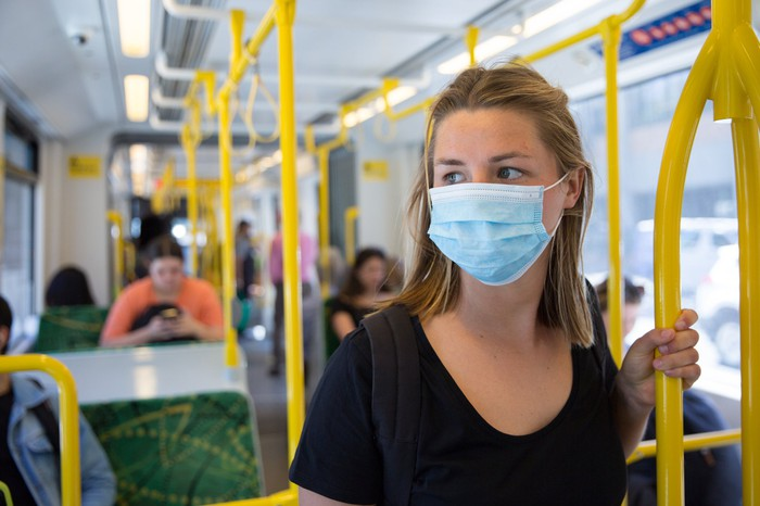 A woman wearing a surgical face mask while on a tram.