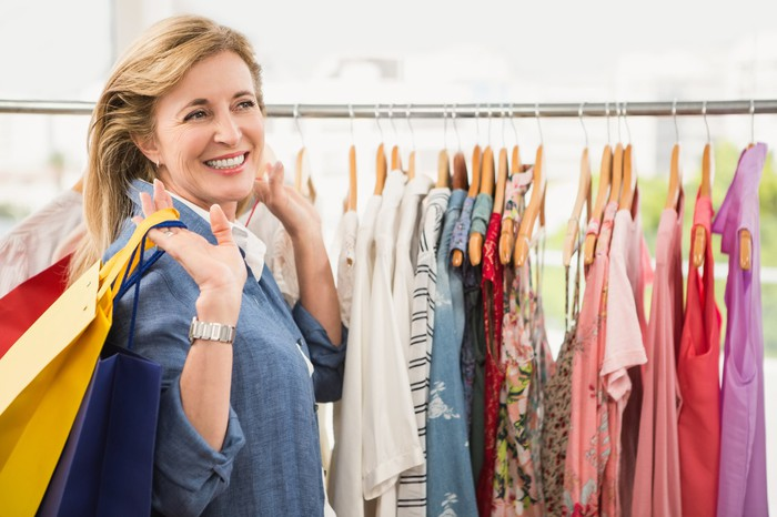 A smiling woman carrying multiple shopping bags in front of a rack of clothes.