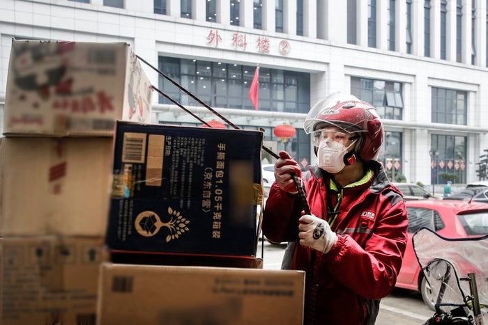 A JD delivery courier in a mask untethers boxes for delivery on the street.