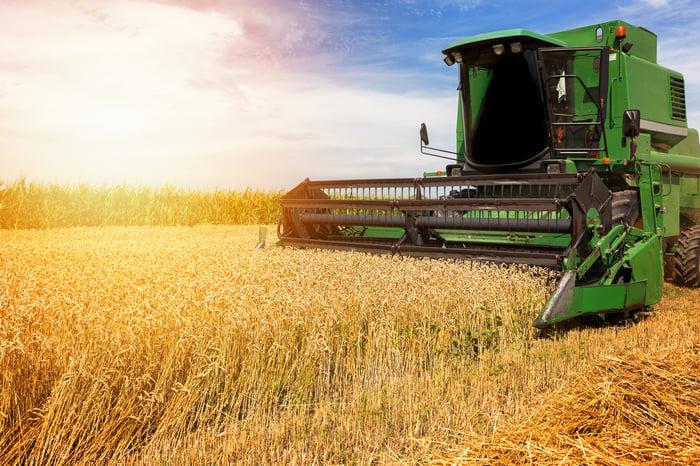 Green Deere combine harvester in the field