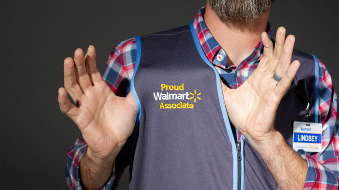 A Walmart employee shows off his work vest.