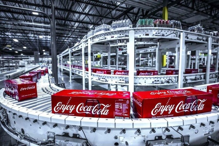 cases of Coca-Cola cans roll along an assembly line conveyor in a bottling plant