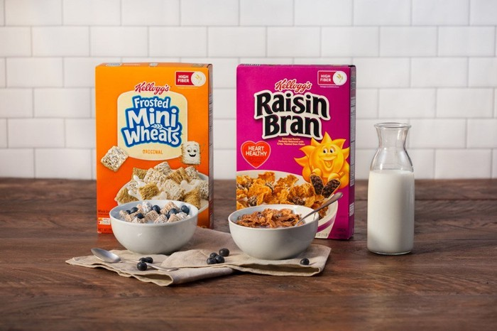 Kellogg cereals Mini Wheats and Raisin Bran sit on a table with bowls and a glass pitcher of milk