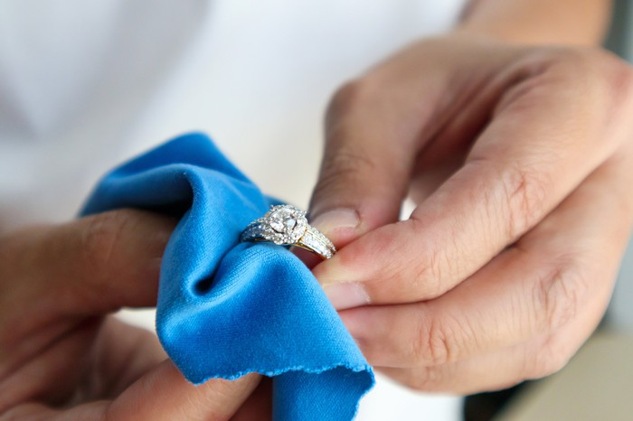 A set of hands cleans a diamond ring with a blue cloth.