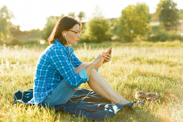 A woman sits in a grass field and listens to an audiobook.