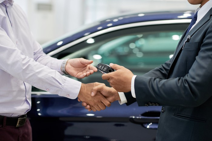 car salesman shaking hands with buyer and handing over keys