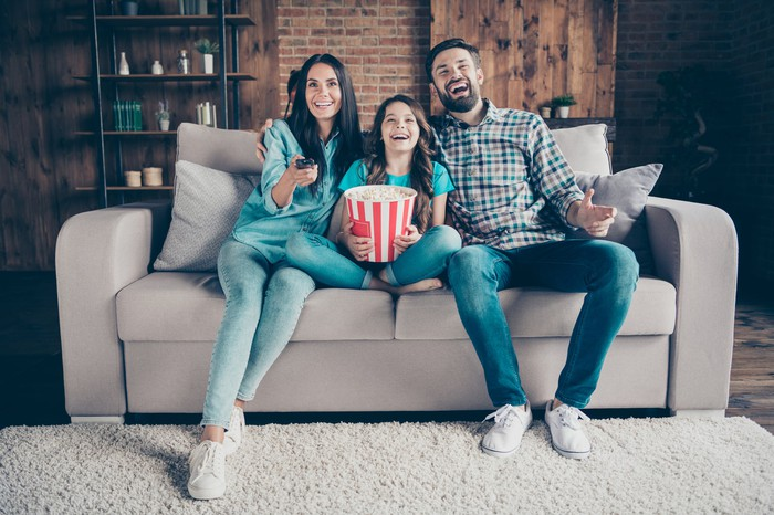Two adults and a child are on a couch.