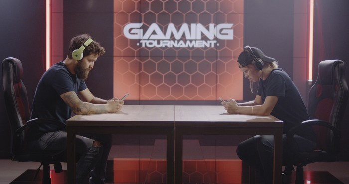 Two men sit across a table holding video game controls with the words Gaming Tournament on a screen behind them.