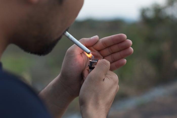 A man lighting a cigarette.