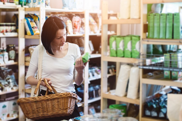 A woman at a store holding a basket while looking at an item.