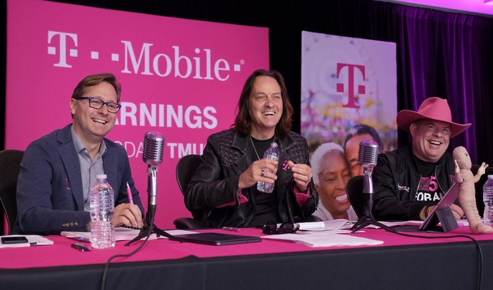 T-Mobile management sitting at a table in front of microphones.