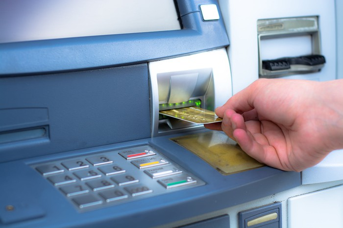 Hand putting an ATM card in a machine.