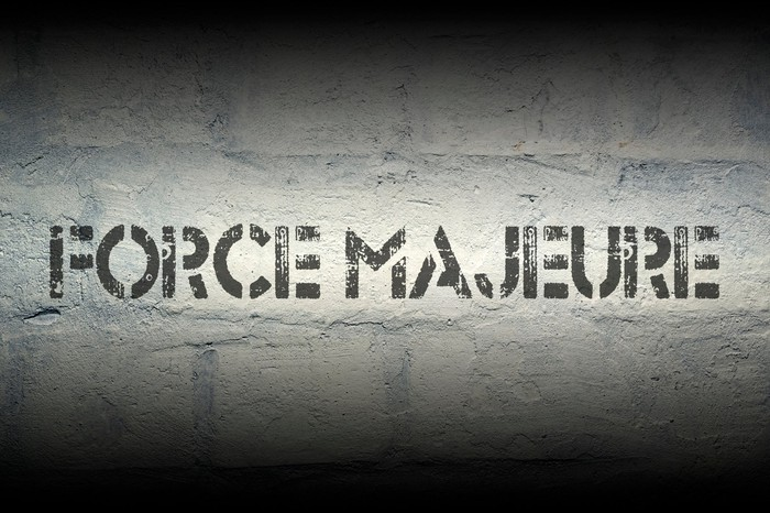 Words Force Majeure stenciled on a wall