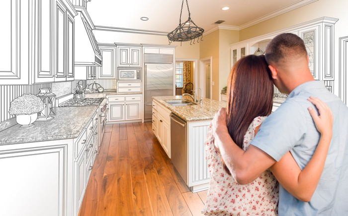 Couple staring at their kitchen covered in a schematic of their future kitchen.