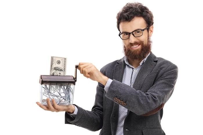 A bearded man shreds a $100 bill.