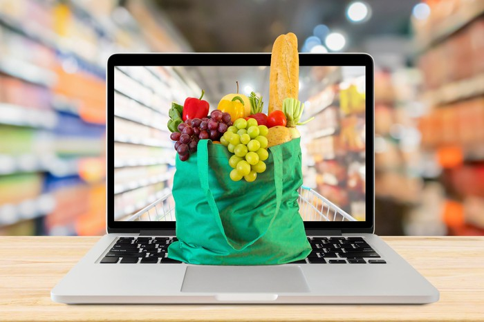 A green shopping bag overflowing with grapes and a loaf of bread sits atop an open computer with a blurred image of shopping aisles in the background.