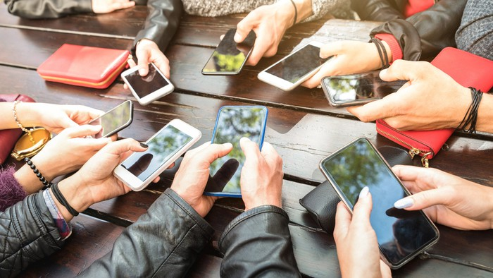 People gathered around a table and looking at their cellphones.