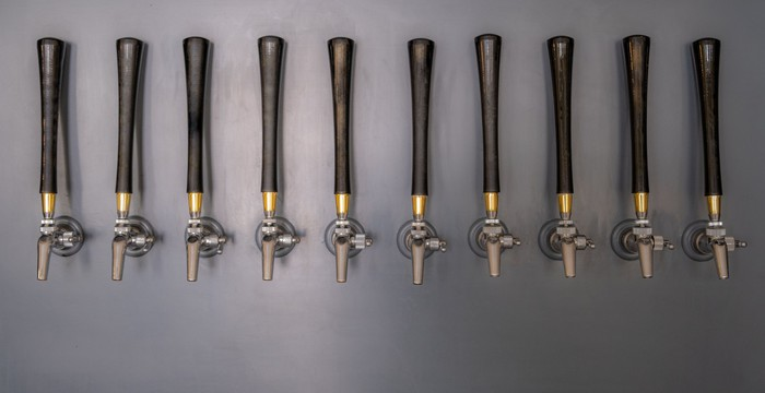10 beer taps with long wood handles mounted on a grey slate wall.