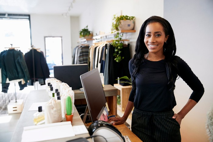 Young woman smiling behind the counter of a retail store.
