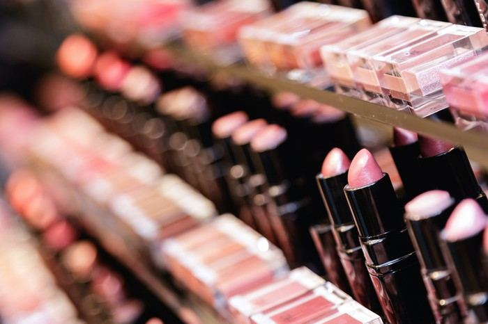 Rows of lipstick and makeup testers in a beauty store.