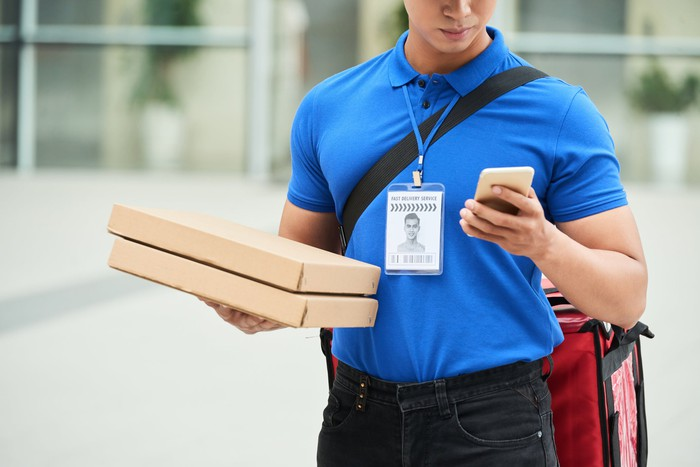 Pizza delivery guy consulting his online app