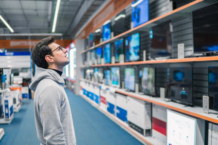 Person looking at monitors in a large retail store.