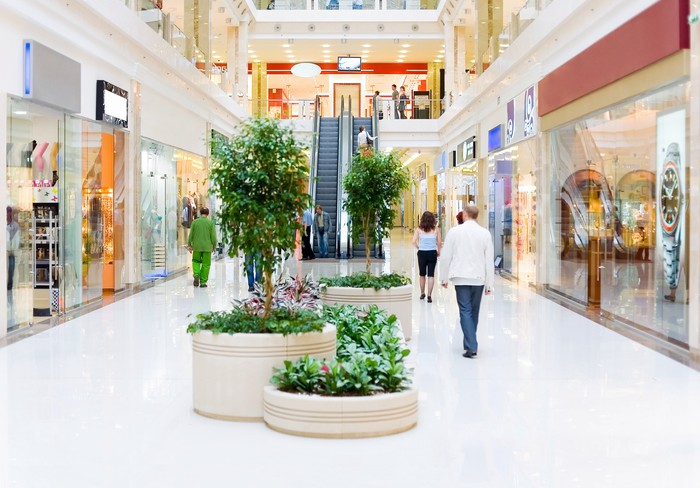 Empty mall corridor, with only a few customers