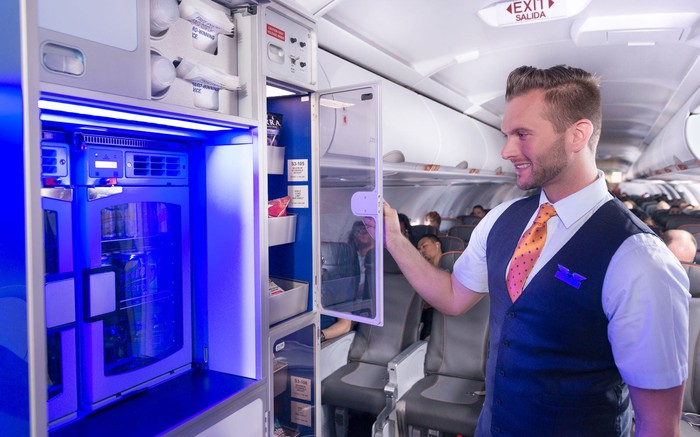A JetBlue flight attendant checking on the snacks and chilled beverages with passengers sitting in the cabin.