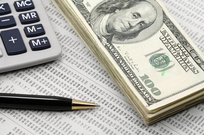 A neat stack of one-hundred-dollar bills, a calculator, and a pen, all lying atop a financial newspaper with stock quotes.