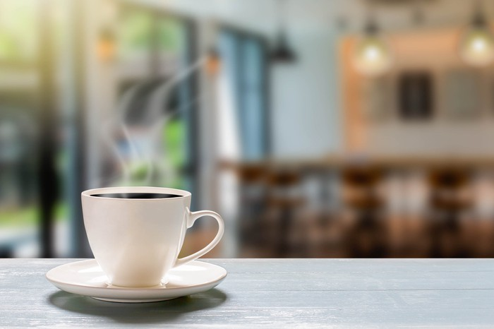 A filled coffee cup and saucer on a table