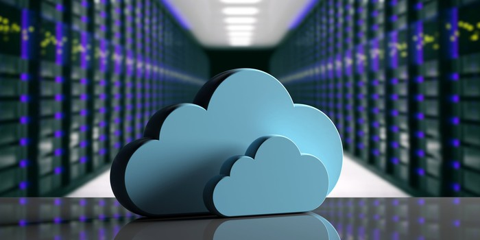 Two baby blue clouds on table in front of blurred computer data center background.