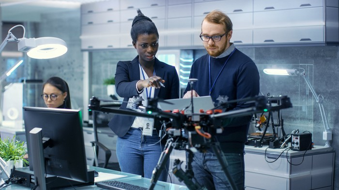 Three people working on a drone in a laboratory
