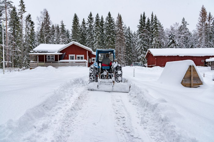A tractor clears snow on a farm.