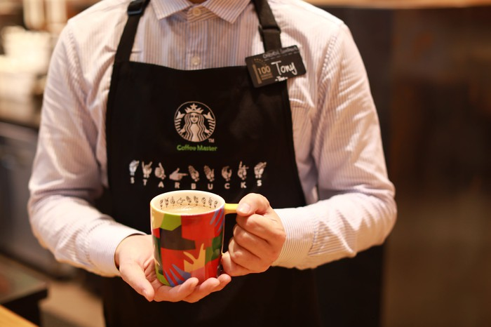 Starbucks partner holding a cup of coffee.