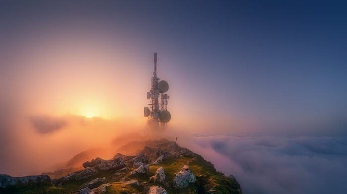 Communication tower on top of a cloud-covered mountain top.