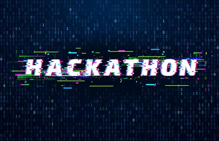 Hackathon sign behind computer code.