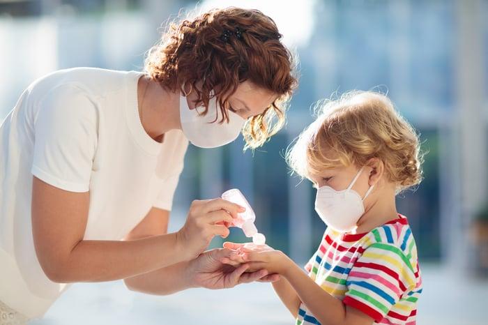 Mom putting hand sanitizer on her child.