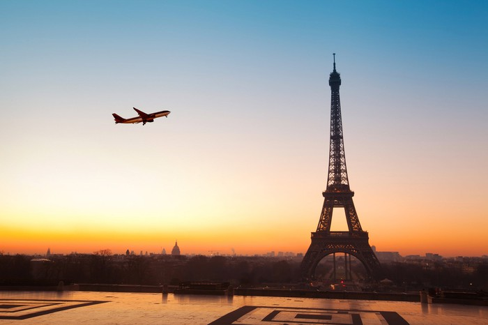 Airplane flying over Eiffel Tower at sunrise