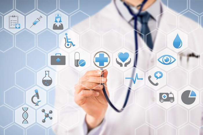 Doctor holding stethoscope up to healthcare-related icons.