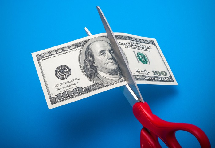 A pair of scissors cuts a hundred-dollar bill.
