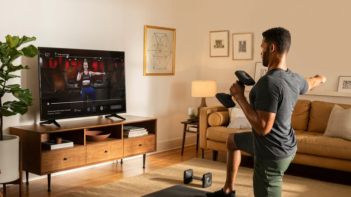 A man exercises in his living room using the Peloton app.
