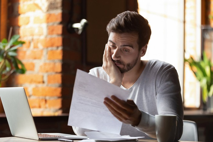 A concerned man looking at a document with his hand on face.