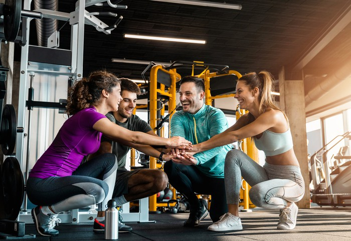 A group of men and women in a workout gym putting their hands together.