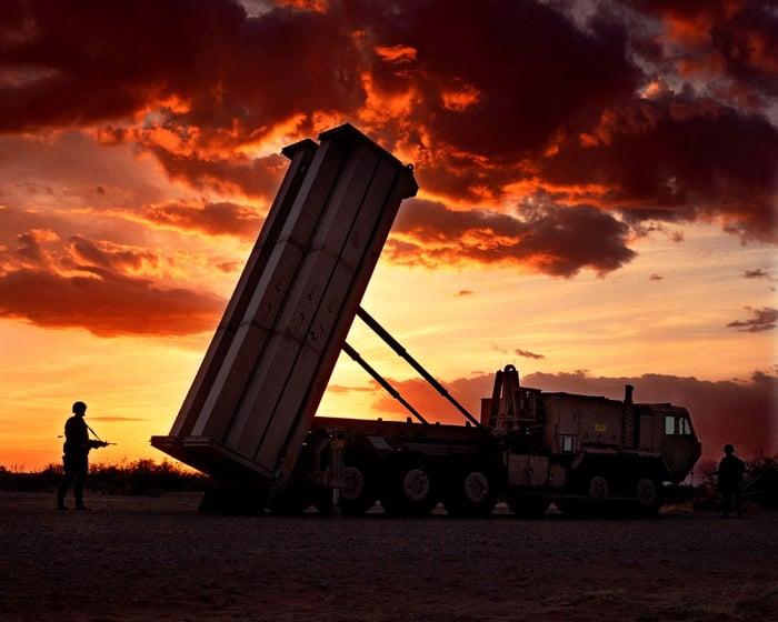 A THAAD unit aims toward the sky as the sun sets behind it.