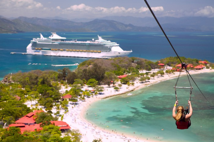 A person ziplines with a cruise ship in the background.