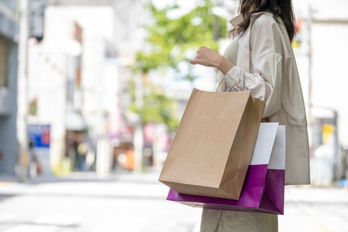 A woman stands outside of a shopping area holding shopping bags.