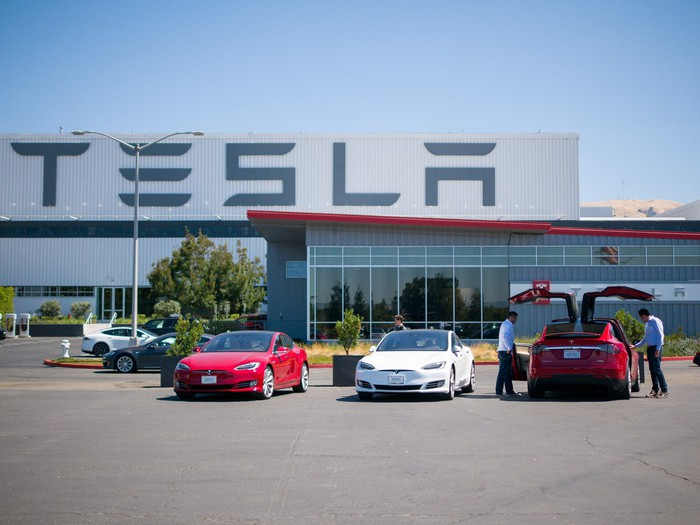 3 Tesla vehicles parked outside of the factory building.