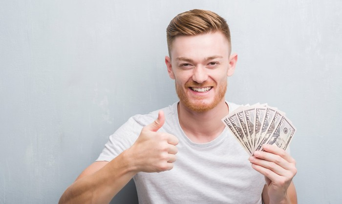 Man holding 100 dollar bills in hand while giving thumbs up.