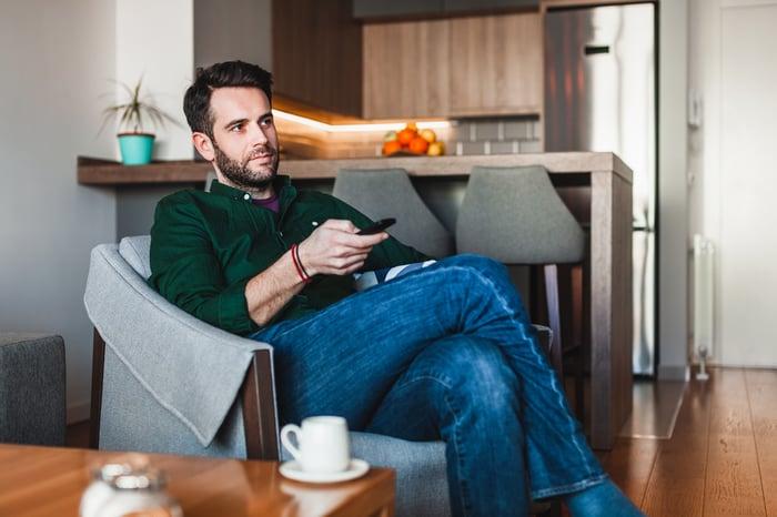 A man watching TV at home.